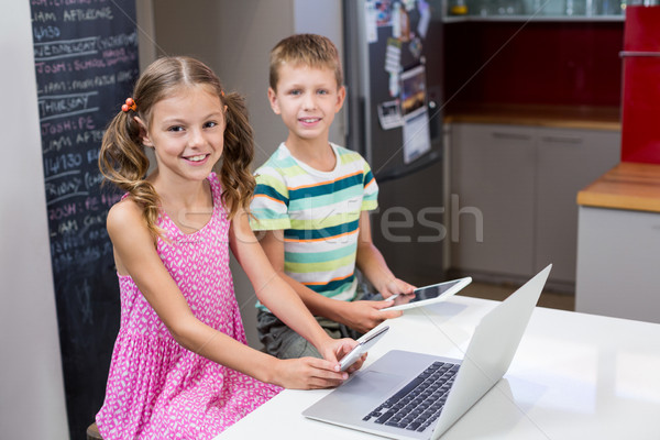Siblings using digital tablet and mobile phone in kitchen Stock photo © wavebreak_media