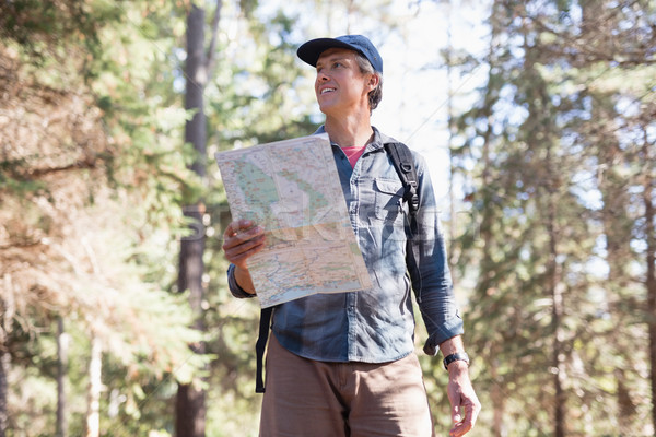 Low angle view of hiker with map standing in forest Stock photo © wavebreak_media