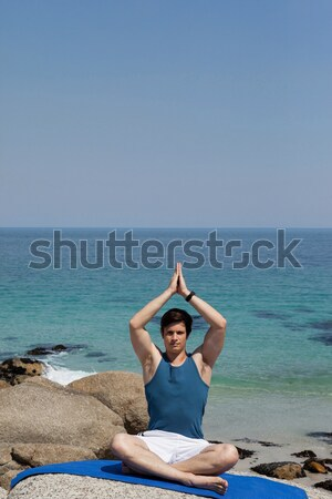 Senior woman practising yoga while sitting against sea Stock photo © wavebreak_media