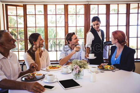 Group of friends interacting with each other while having meal together Stock photo © wavebreak_media