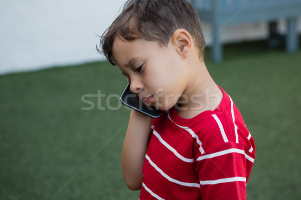 Close up of boy talking on mobile phone while standing on field Stock photo © wavebreak_media