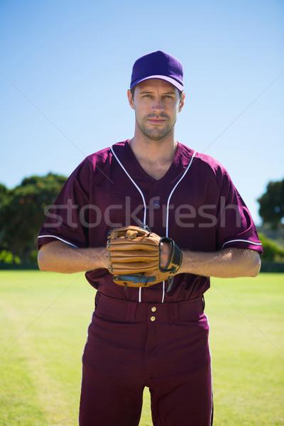 Portrait of confident baseball pitcher standing against sky Stock photo © wavebreak_media