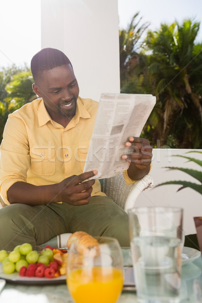 Happy young man reading newspaper at cafe Stock photo © wavebreak_media