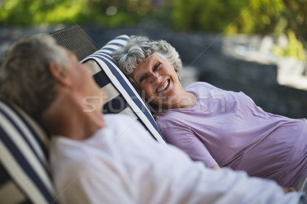 Smiling senior woman looking at man resting on lounge chair Stock photo © wavebreak_media