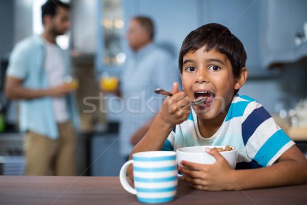 Portrait of boy having breakfast with family in background Stock photo © wavebreak_media