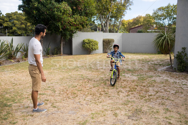 Father looking at son riding bicycle Stock photo © wavebreak_media