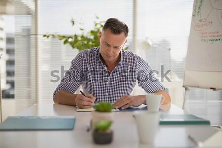 Graphic designer writing on tablet at desk in studio Stock photo © wavebreak_media