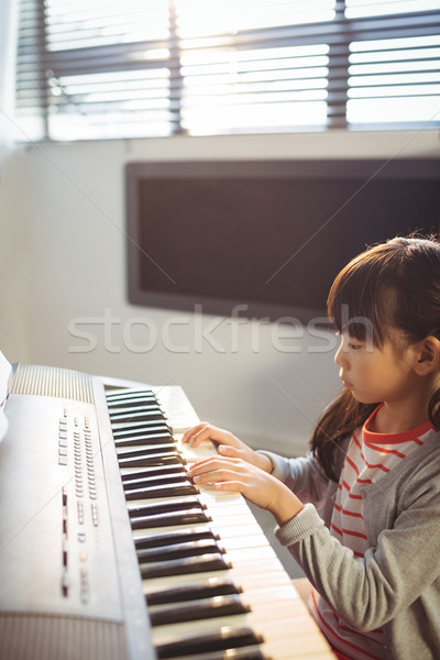 High angle view of concentrated girl practicing piano in class Stock photo © wavebreak_media