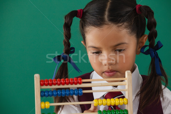 Schoolgirl using abacus against chalkboard Stock photo © wavebreak_media