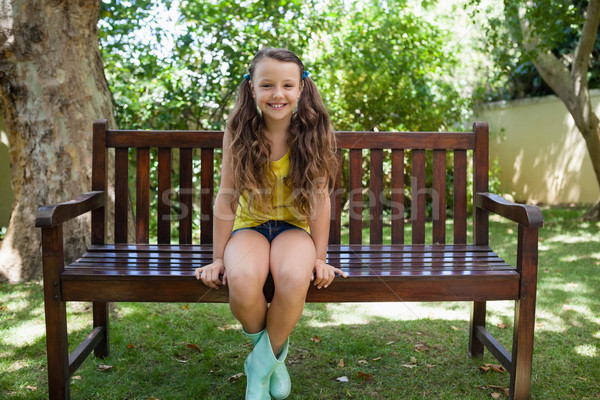 Portrait of smiling girl sitting on wooden bench Stock photo © wavebreak_media