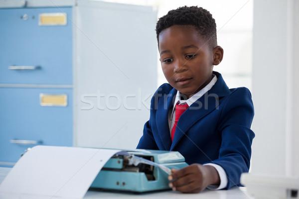 Boy imitating as businessman working on typewriter Stock photo © wavebreak_media