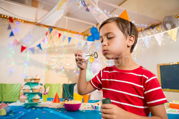 Stock photo: Cute boy playing with bubble wand during birthday party