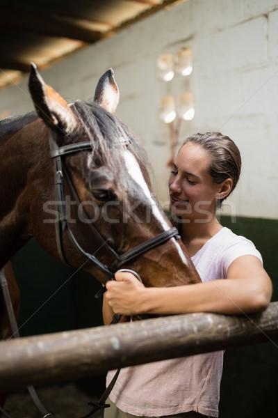 Souriant jockey permanent cheval écurie femme Photo stock © wavebreak_media