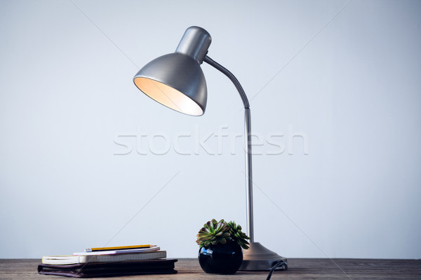 Illuminated desk lamp by books on table by wall in office Stock photo © wavebreak_media