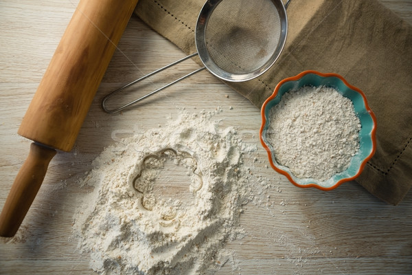 Overhead view of flour in bowl by rolling pin and strainer Stock photo © wavebreak_media