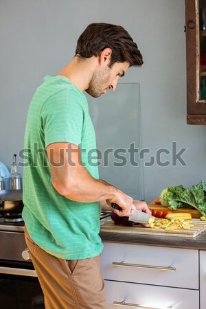 Kind father helping his daughter slicing vegetables Stock photo © wavebreak_media