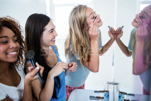 Three smiling friends putting makeup on together Stock photo © wavebreak_media