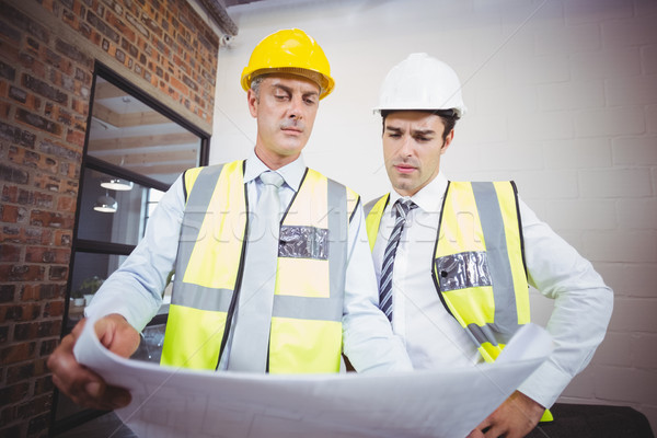 Architects working while holding blueprint  Stock photo © wavebreak_media