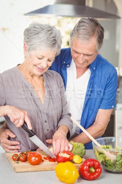Senior woman cutting while man embracing in kitchen Stock photo © wavebreak_media