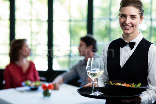 Waitress holding meal and wine glasses in restaurant Stock photo © wavebreak_media