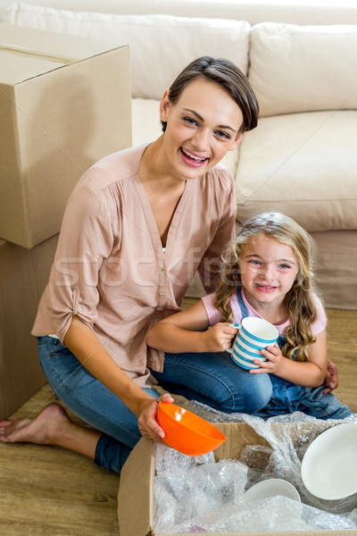 Mother and daughter unpacking box in new house Stock photo © wavebreak_media