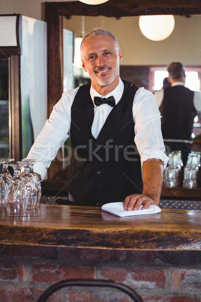 Portrait of bartender cleaning bar counter Stock photo © wavebreak_media
