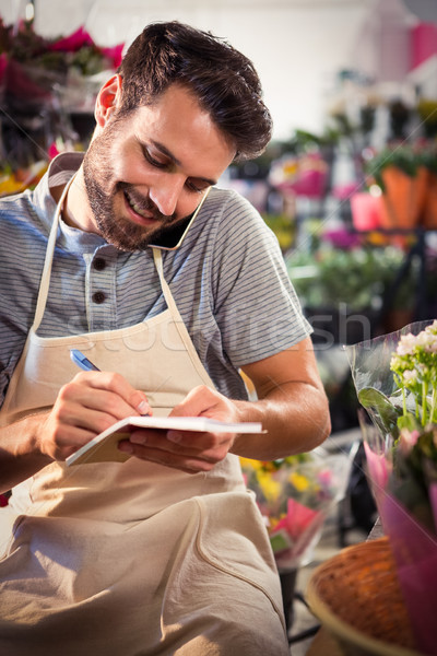 Male florist noting order in diary while talking on mobile phone Stock photo © wavebreak_media
