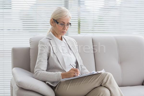 Terapeuta piśmie zauważa koncentruje sofa biuro Zdjęcia stock © wavebreak_media