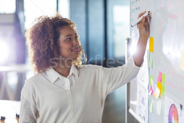 Femme écrit femme souriante bureau affaires Photo stock © wavebreak_media