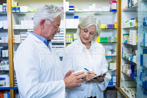 Pharmacists checking and writing prescription for medicine Stock photo © wavebreak_media