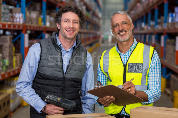 Portrait of warehouse workers standing with clipboard and barcode scanner Stock photo © wavebreak_media