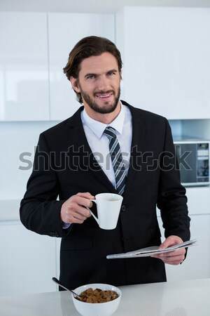 Stock photo: Businessman reading newspaper while having coffee in kitchen