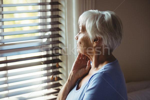 Zamyślony starszy kobieta patrząc na zewnątrz okno Zdjęcia stock © wavebreak_media