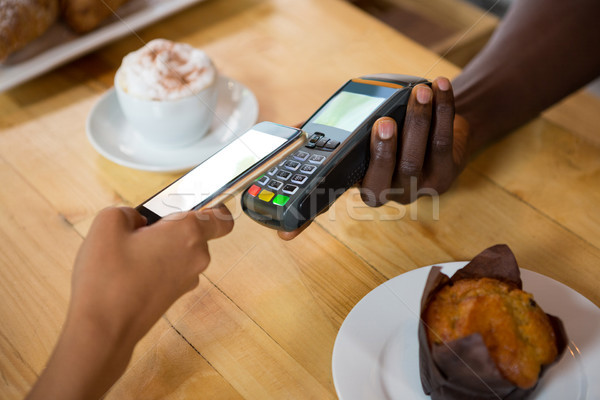 Barista accepting payment through mobile phone at cafe Stock photo © wavebreak_media