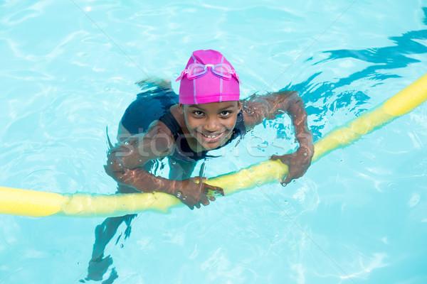 Portrait of girl swimming with pool noodle Stock photo © wavebreak_media