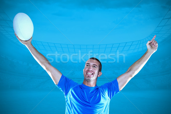 Composite image of happy rugby player in blue jersey holding bal Stock photo © wavebreak_media