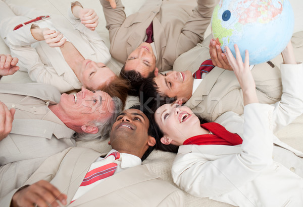 Business team lying on the floor playing with a terrestrial glob Stock photo © wavebreak_media