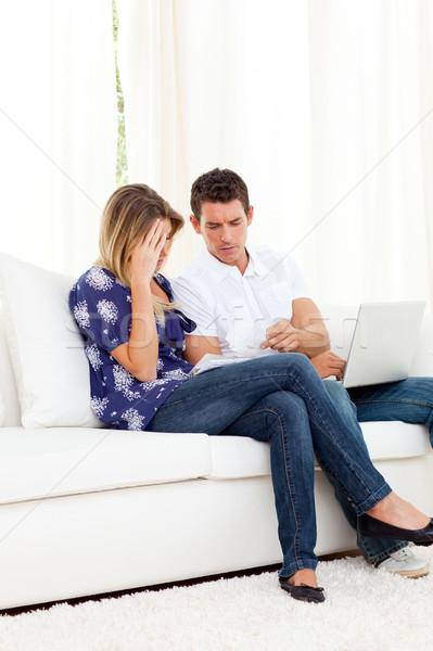 Distressed couple doing their accounts sitting on sofa Stock photo © wavebreak_media