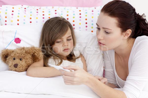 Mother taking sick daughter's temperature Stock photo © wavebreak_media