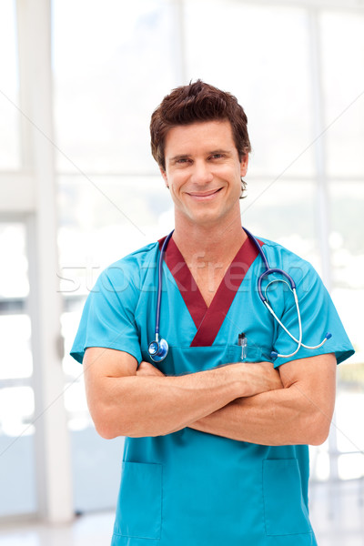 Portrait of a confident doctor in blue scrubs smiling at camera Stock photo © wavebreak_media