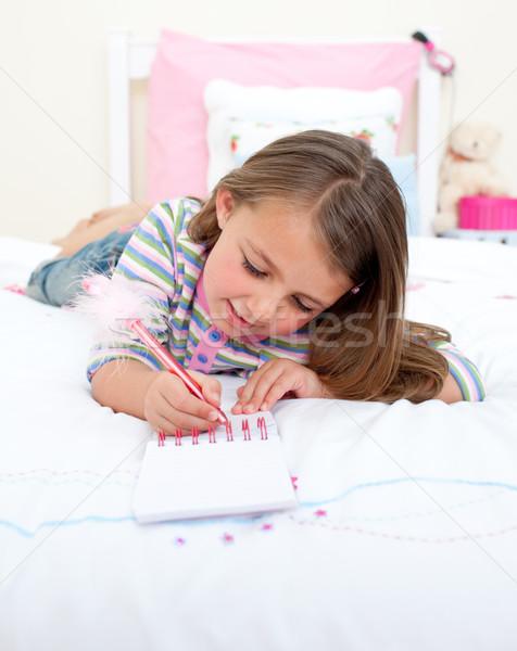 Konsantre küçük kız yazı defter yatak gülümseme Stok fotoğraf © wavebreak_media