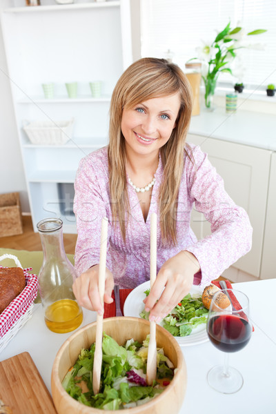 Portrait of a cute woman serving salad sitting in the kitchen and smiling at the camera Stock photo © wavebreak_media