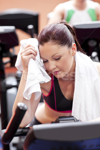 Exhausted woman wiping her face with a towel sitting on a cross trainer in a sport centre Stock photo © wavebreak_media