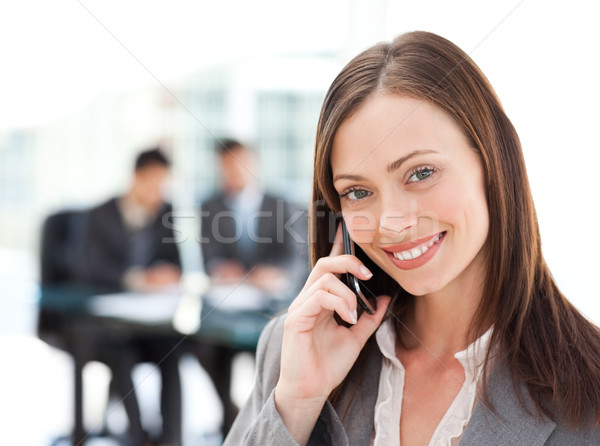Captivating businesswoman on the phone while her team is working Stock photo © wavebreak_media