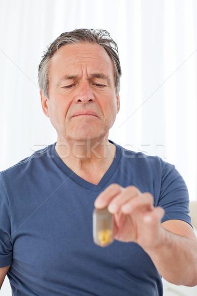 Sick man taking his pills at home Stock photo © wavebreak_media
