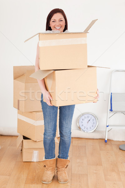 Stock photo: Good looking red-haired woman holding some carboard boxes at home