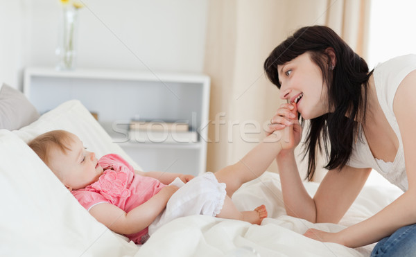 Stock photo: Good looking brunette female playing with her baby while sitting on a bed in her appartment