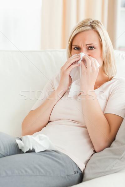 Portrait of a sick woman blowing her nose in her living room Stock photo © wavebreak_media