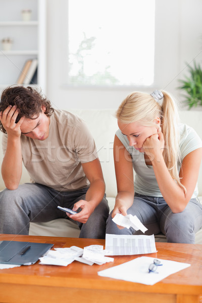 Calculating couple on a sofa in their living room Stock photo © wavebreak_media