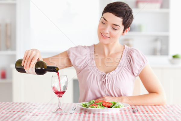 Woman pouring wine in a glass in a kitchen Stock photo © wavebreak_media